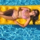 Beautiful Girl in Sunglasses and Bikini Lying on Yellow Inflatable Mattress in Swimming Pool. Young - VideoHive Item for Sale