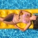 Top View of Beautiful Tanned Girl in Sunglasses and Pink Bikini Lying on Yellow Inflatable Mattress - VideoHive Item for Sale