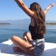 Young girl sitting on bow of boat, looking to beautiful landscape and raising hands to enjoy freedom - VideoHive Item for Sale