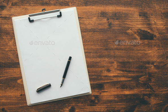 Overhead view of blank clipboard note pad paper with pen - Stock Photo - Images