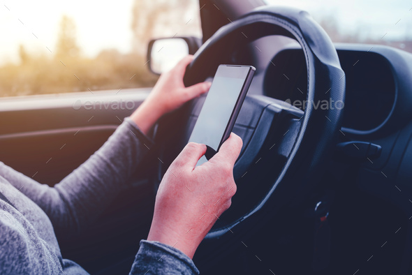 Woman simultaneously driving car and reading text message - Stock Photo - Images