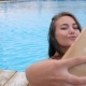 Girl in Swimsuit Makes Photo with Colorful Beverage on Swimming-pool Edge - VideoHive Item for Sale