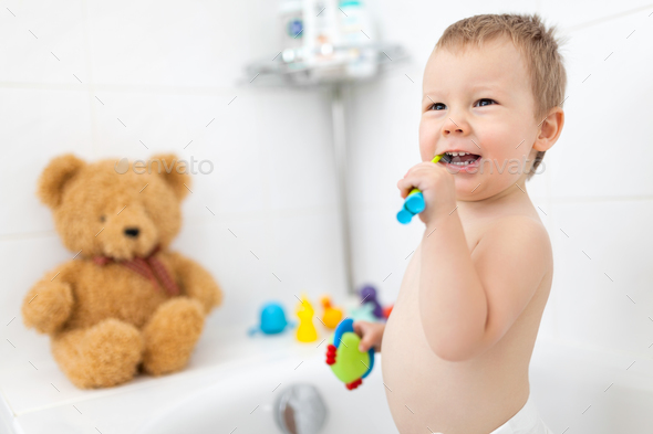 Adorable child learing how to brush his teeth - Stock Photo - Images
