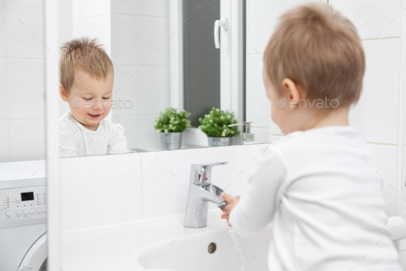 Cute toddler learning how to wash his face - Stock Photo - Images