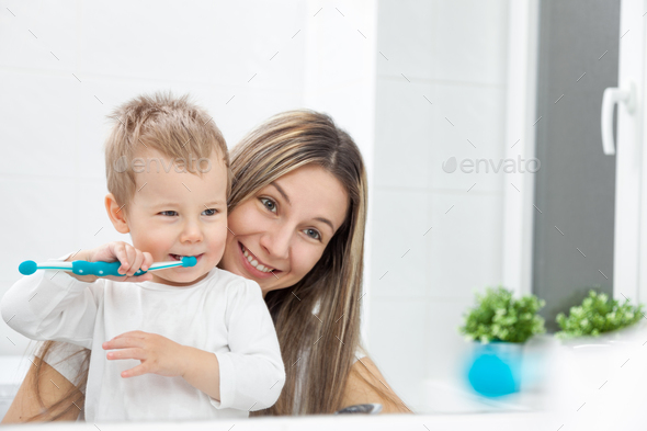 Happy mother teaching her son how to bush teeth - Stock Photo - Images