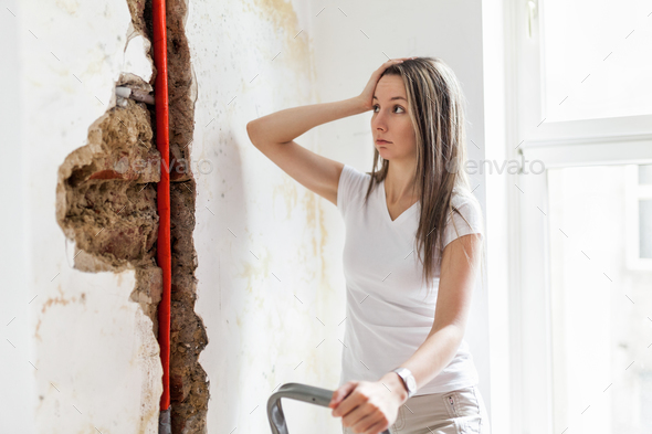 Woman looking at damage after a water pipe leak - Stock Photo - Images