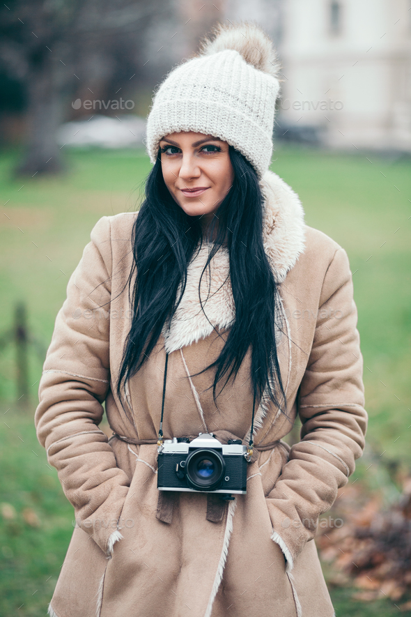 Female photographer taking pictures outdoors with a vintage camera - Stock Photo - Images
