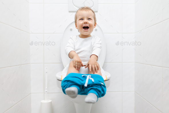 Adorable young child sitting on the toilet - Stock Photo - Images
