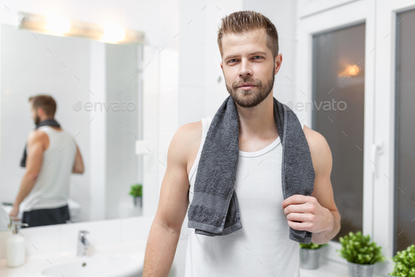 Morning hygiene, Man in the bathroom looking in mirror - Stock Photo - Images