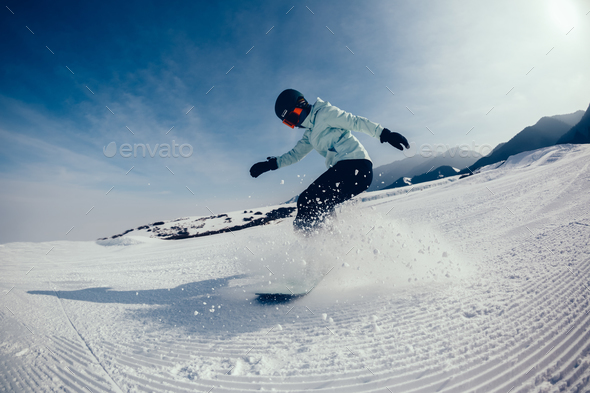 female snowboarder descent on winter mountain slope - Stock Photo - Images