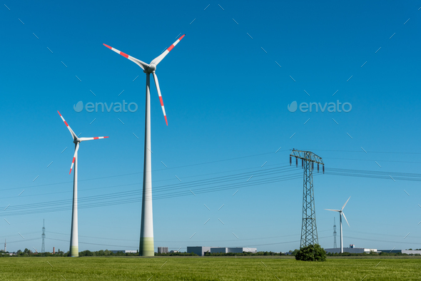 Wind turbines and overhead lines on a sunny day - Stock Photo - Images