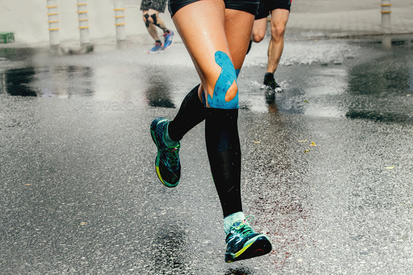 legs runner woman with kinesio tape - Stock Photo - Images