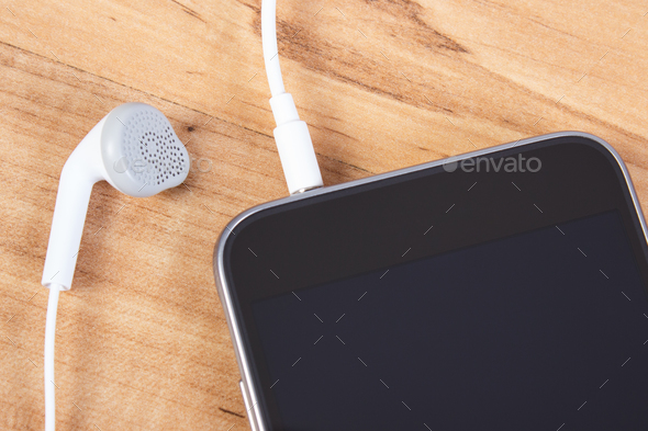 Mobile phone with headphones, using smartphone concept - Stock Photo - Images