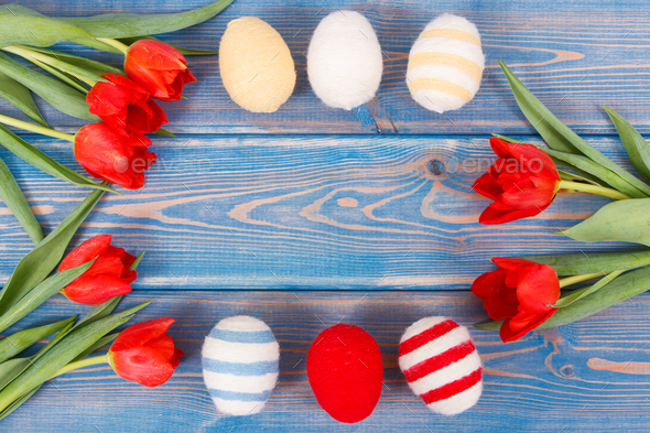 Bouquet of red tulips and Easter eggs wrapped woolen string, festive decoration - Stock Photo - Images