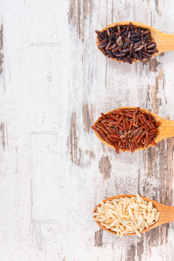 Brown, black and red rice on wooden spoons, healthy gluten free food concept, copy space for text - Stock Photo - Images