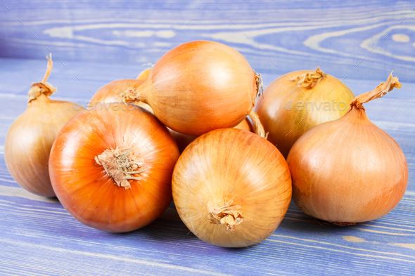 Heap of onions on purple boards, healthy nutrition - Stock Photo - Images