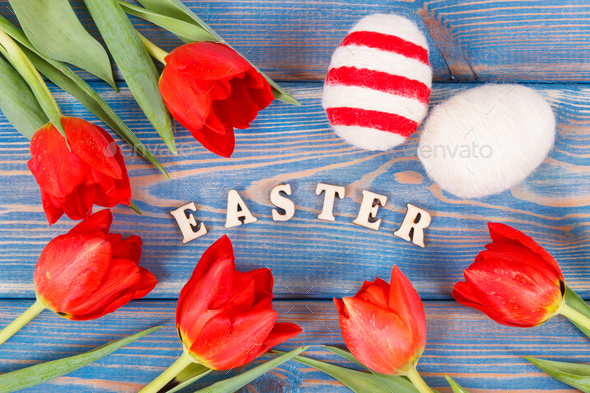 Easter eggs and fresh red tulips on boards, festive decoration - Stock Photo - Images