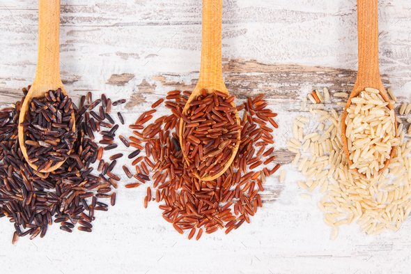 Brown, red and black rice on wooden spoon, healthy nutrition concept - Stock Photo - Images