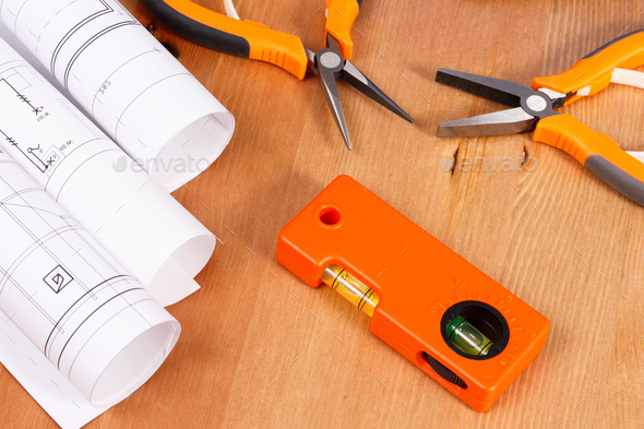 Rolls of electrical drawings or blueprints and orange work tools for use in engineer jobs - Stock Photo - Images