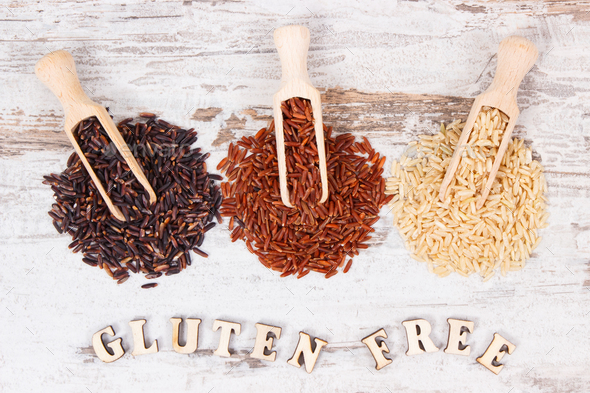 Inscription gluten free with brown, black and red rice on wooden scoops, healthy food concept - Stock Photo - Images