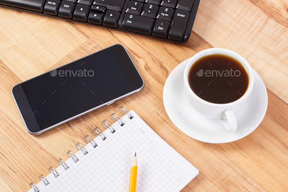 Mobile phone with notepad for writing notes and cup of coffee, using electronics concept - Stock Photo - Images