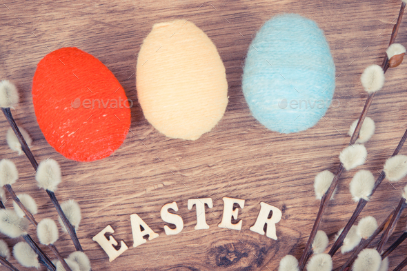 Inscription Easter, catkins and eggs wrapped woolen string - Stock Photo - Images
