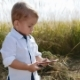 Sweet Baby-blogger Stands in the Middle of Field, Uses Smartphone, Playing Games, Posting Photos - VideoHive Item for Sale