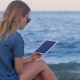 Lonely Pretty Blonde Woman Is Reading E-book By Tablet, Sitting on Sea Beach in Evening - VideoHive Item for Sale
