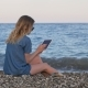 Slim Blonde Woman Looking Photo By Tablet, Sitting on Pebble Beach, Back View, Static Shot,sea Surf - VideoHive Item for Sale