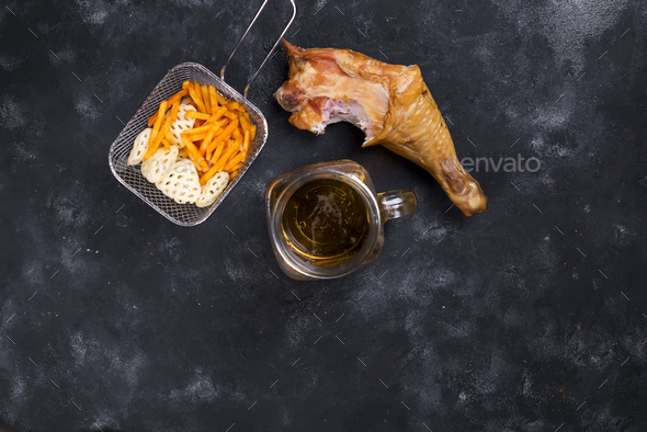 glass of beer and around snacks and smoked chicken thighs - Stock Photo - Images