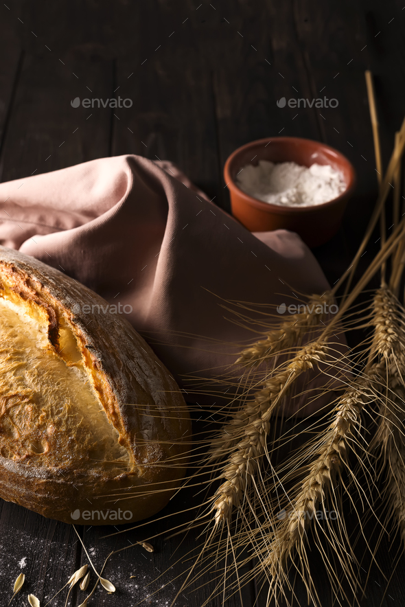 Fresh bread with wheat on wooden table - Stock Photo - Images