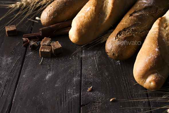 Bakery - gold rustic crusty loaves of bread and buns on black chalkboard background. - Stock Photo - Images
