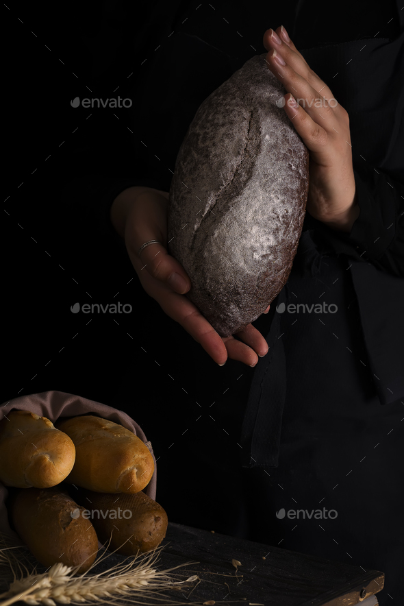 Woman holding tasty fresh bread, close up - Stock Photo - Images