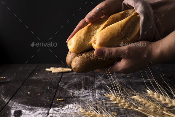 Baker woman holding rustic organic loaf of bread in hands - rural baker - Stock Photo - Images