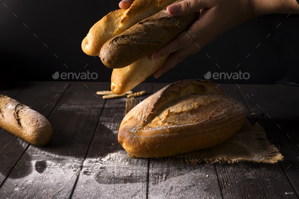 Close-up of woman hands take fresh bread. Dark photo - Stock Photo - Images
