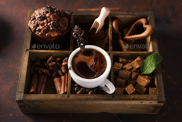 Chocolate muffins with cup of coffee on a wooden box with grains of coffee and spices - Stock Photo - Images