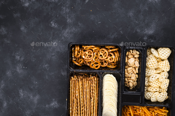 a variety of snacks on the box for beer on a concrete black table - Stock Photo - Images
