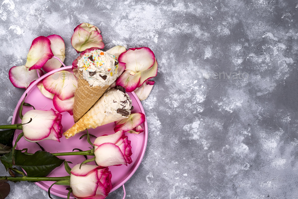 Composition of ice cream waffles with roses bouquets on a stone background - Stock Photo - Images
