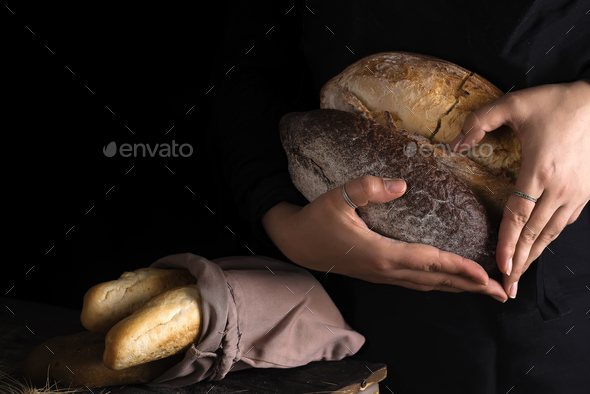 Close-up of woman hands as heart take fresh bread. Dark photo - Stock Photo - Images