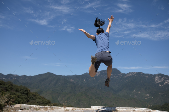 hipster woman jumping on top of great wall in china - Stock Photo - Images