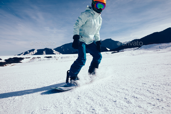 woman snowboarder descent on winter mountain slope - Stock Photo - Images