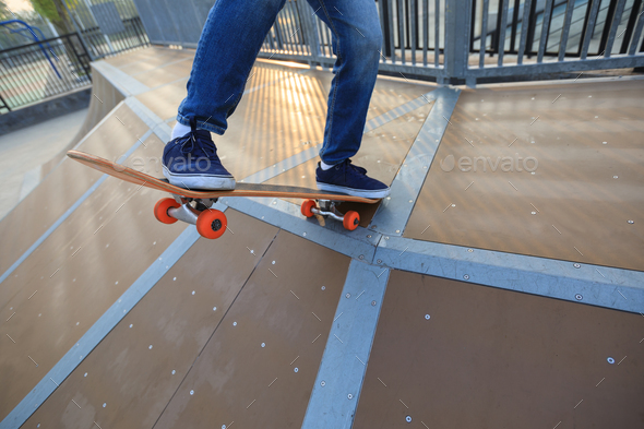 Skateboarder going to descent a ramp at skatepark - Stock Photo - Images
