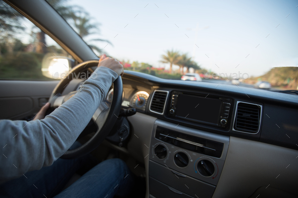 Hands on wheel driving car in morning tropical city - Stock Photo - Images