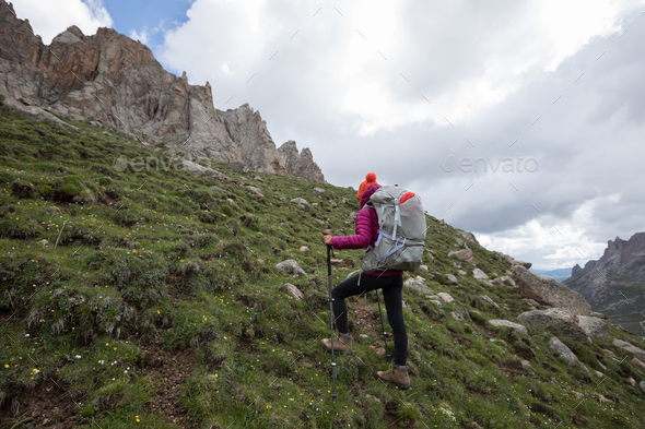 Woman hiker with heavy backpack ascent on high altitude mountain - Stock Photo - Images