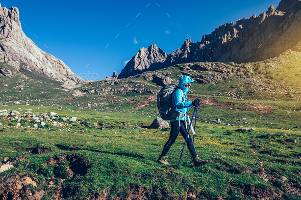 Woman with backpack hiking on high altitude mountains - Stock Photo - Images