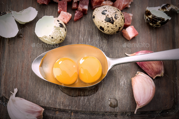 overhead shot of raw eggs and open quail in metal spoon, on rustic wood - Stock Photo - Images