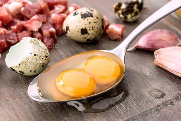 Raw eggs and open quail in metal spoon, on rustic wood - Stock Photo - Images