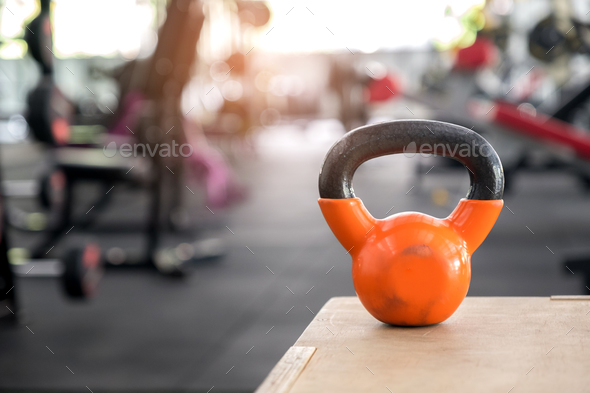 Orange kettlebell put on a wooden crate. - Stock Photo - Images