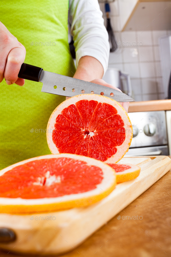 Woman's hands cutting grapefruit - Stock Photo - Images