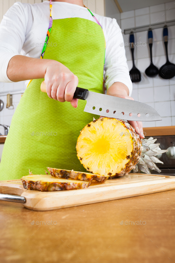 Woman's hands cutting pineapple - Stock Photo - Images